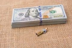 Équipez la figurine près du paquet du billet de banque de dollar US Photos libres de droits