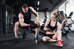 Équipez la formation avec l'haltère tandis que femme à l'aide du smartphone Photo libre de droits