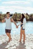 Équipez la guitare de transport et des mains de se tenir avec son amie sur la plage sablonneuse Image stock