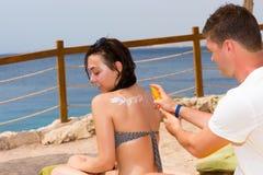 Équipez la lotion de protection solaire de frottage sur le dos de la jeune femme Images libres de droits