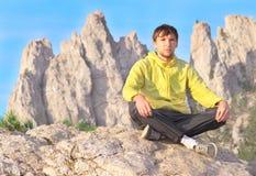 Équipez la méditation de détente de yoga de voyageur se reposant sur des pierres avec Rocky Mountains Photos stock