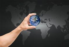 Équipez la main attrapant la terre sur la carte du monde, éléments de cette image Photographie stock libre de droits