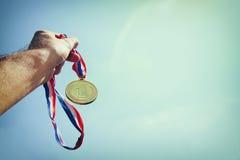 Équipez la main augmentée, en tenant la médaille d'or contre le ciel concept de récompense et de victoire Foyer sélectif Rétro im Photos stock