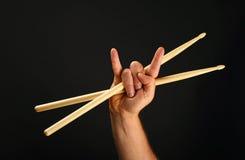 Équipez la main avec le pilon et les klaxons croisés de diable au-dessus du noir Image libre de droits