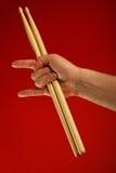 Équipez la main avec le pilon et les klaxons de diable au-dessus du rouge Photographie stock