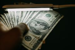 Équipez la main avec une pile de cent factures de dollars US au-dessus de billet de banque photographie stock libre de droits