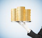 Équipez la main dans le gant blanc tenant un plateau avec un pille des pièces de monnaie Image stock