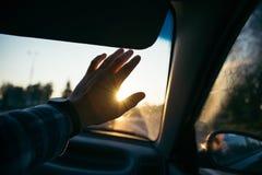Équipez la main de prise devant le soleil sur le coucher du soleil Photo stock
