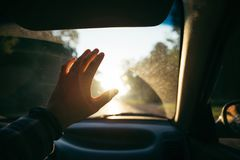 Équipez la main de prise devant le soleil sur le coucher du soleil Photo libre de droits