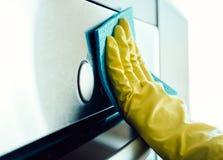 Équipez la main du ` s nettoyant le four de cuisine Image libre de droits