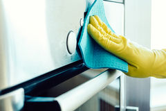 Équipez la main du ` s nettoyant le four de cuisine Images stock