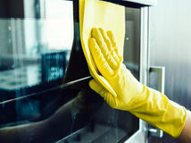 Équipez la main du ` s nettoyant le four de cuisine Photo stock