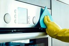 Équipez la main du ` s nettoyant le four de cuisine Photographie stock