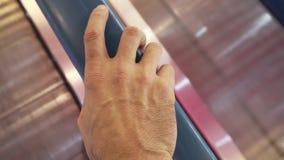 Équipez la main du ` s sur la balustrade d'un travelator banque de vidéos