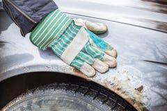 Équipez la main du ` s sur l'amortisseur rouillé de voiture Photo stock