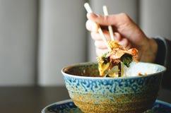 Équipez la main du ` s tenant des baguettes au-dessus d'un plat de repas japonais, thaïlandais, chinois - riz, champignon, légume photos stock