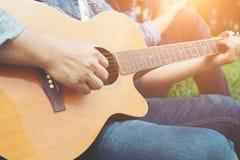 Équipez la main du ` s tenant des cordes de guitare, train tout le temps Photographie stock