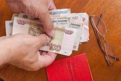 Équipez la main du ` s tenant l'argent, les verres et le certificat de pension sur une traduction surface-anglaise en bois : cert Photo libre de droits