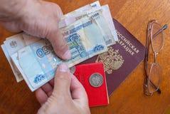 Équipez la main du ` s tenant l'argent, les verres et le certificat de pension sur une traduction surface-anglaise en bois : cert Photographie stock libre de droits