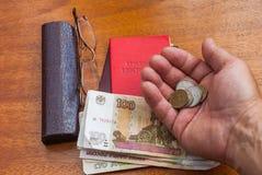 Équipez la main du ` s tenant l'argent, les verres et le certificat de pension sur une traduction surface-anglaise en bois : cert Images libres de droits