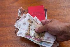 Équipez la main du ` s tenant l'argent, les verres et le certificat de pension sur une traduction surface-anglaise en bois : cert Photos stock
