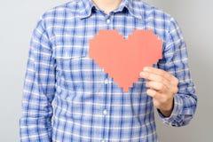 Équipez la main du ` s tenant le coeur de papier rouge de pixel Photos stock