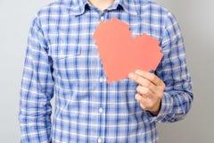 Équipez la main du ` s tenant le coeur de papier rouge de pixel Photo stock