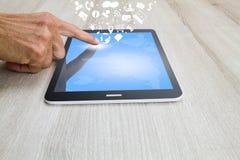 Équipez la main du ` s touchant sur la tablette avec la carte du monde, le social et les icônes d'affaires sur le bureau en bois Photos libres de droits
