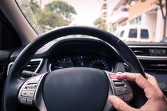 Équipez la main du ` s touchant un bouton d'ecall dans la voiture du ` s de roues photo libre de droits