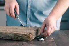Équipez la main du ` s utilisant la planche d'Assembling Wooden de tournevis photo stock