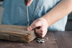 Équipez la main du ` s utilisant la planche d'Assembling Wooden de tournevis images stock