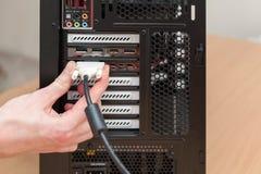 Équipez la main reliant le câble de DVI pour le moniteur au PC d'ordinateur image libre de droits