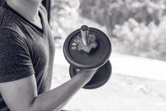 Équipez la main soulevant l'haltère en acier dans une image de gymnase, une vie et un concept noirs et blancs renforcement de mus Photo stock