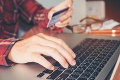 Équipez la main tenant la carte de crédit utilisant la banque en ligne d'ordinateur portable de clavier Image stock