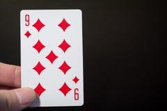 Équipez la main tenant jouer les cartes neuf des diamants d'isolement sur le fond noir avec l'abrégé sur copyspace Photographie stock