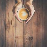 Équipez la main tenant la tasse chaude de café, et de forme de coeur Photographie stock