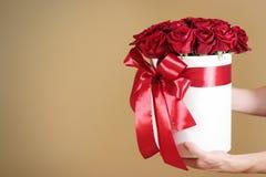Équipez la main tenant le bouquet riche de cadeau de 21 roses rouges composition Photographie stock libre de droits