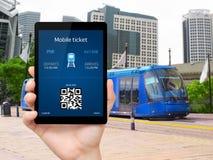 Équipez la main tenant le comprimé avec un ticke mobile de portefeuille et de train Images libres de droits