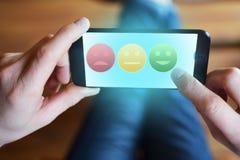 Équipez la main tenant le smartphone avec des icônes d'estimation sur l'écran tactile photo stock