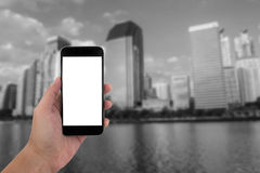 Équipez la main tenant le téléphone et l'écran blanc avec le noir de tache floue et Images stock