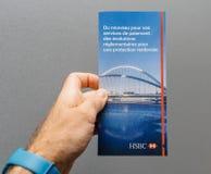 : Équipez la main tenant sur le fond gris l'interdiction officielle de HSBC Photographie stock libre de droits