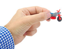 Équipez la main tenant un jouet en plastique de bicyclette sur le blanc Image stock