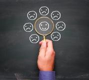 Équipez la main tenant une loupe et des découvertes un visage heureux Images libres de droits