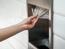 Équipez la main tirant un papier de soie de soie de boîte de tissu dans les toilettes photos libres de droits