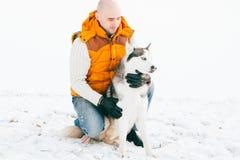 Équipez la marche avec l'horaire d'hiver de chien avec la neige dans l'amitié de chiens de traîneau de forêt Images stock