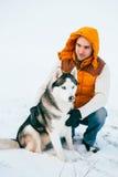 Équipez la marche avec l'horaire d'hiver de chien avec la neige dans l'amitié de chiens de traîneau de forêt Photo libre de droits