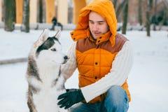 Équipez la marche avec l'horaire d'hiver de chien avec la neige dans l'amitié de chiens de traîneau de forêt Photos stock