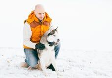Équipez la marche avec l'horaire d'hiver de chien avec la neige dans l'amitié de chiens de traîneau de forêt Photos libres de droits