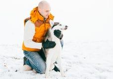 Équipez la marche avec l'horaire d'hiver de chien avec la neige dans l'amitié de chiens de traîneau de forêt Photographie stock