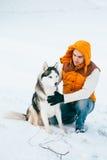 Équipez la marche avec l'horaire d'hiver de chien avec la neige dans l'amitié de chiens de traîneau de forêt Photographie stock libre de droits